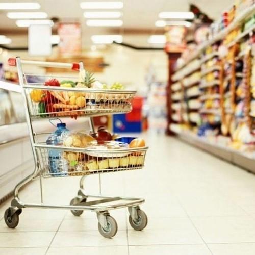 Тележка с продуктами на фоне интерьера супер-маркета
