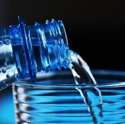 Вода льётся из бутылки в стакан
